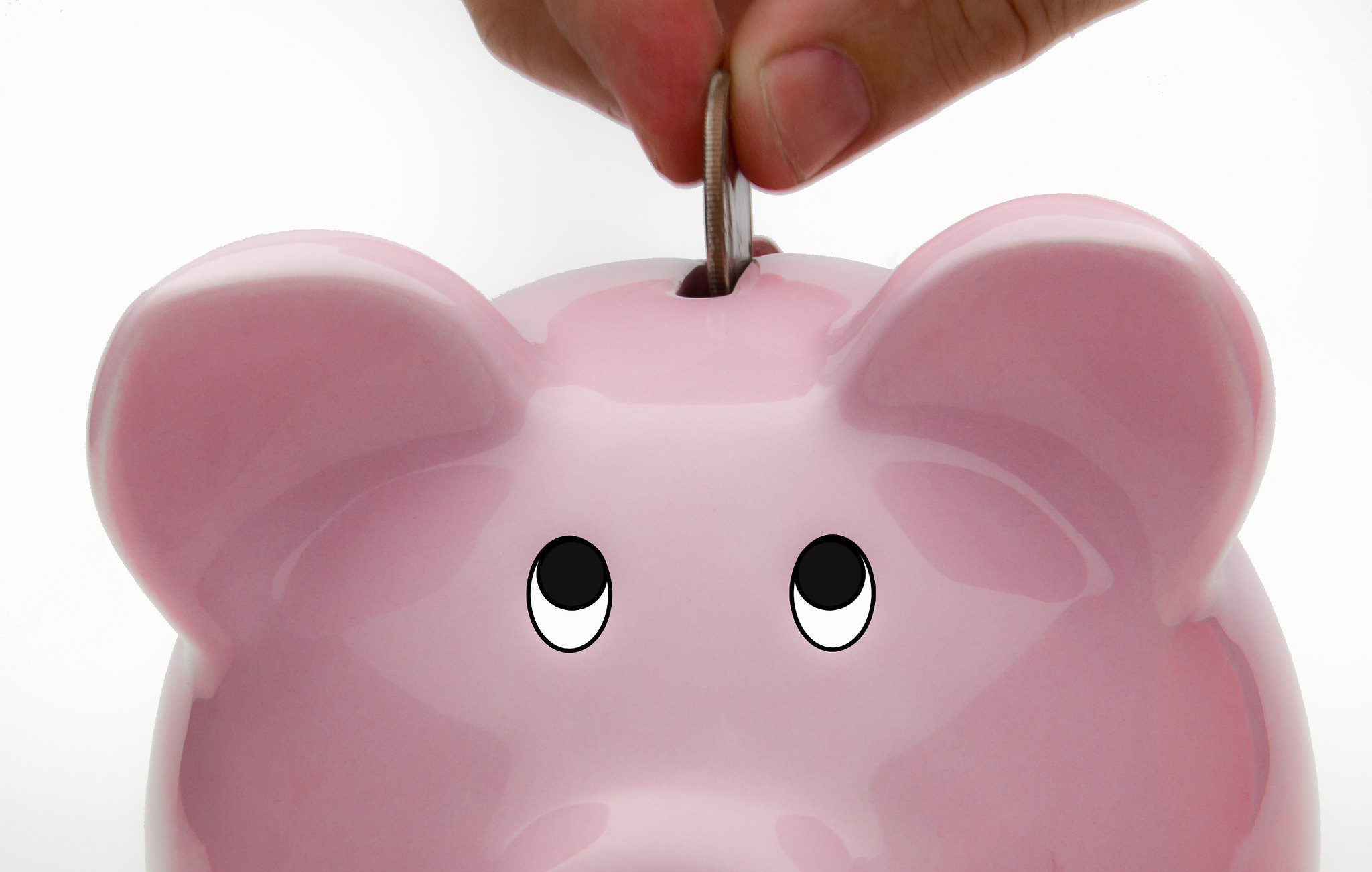 Coin being dropped into a piggy bank