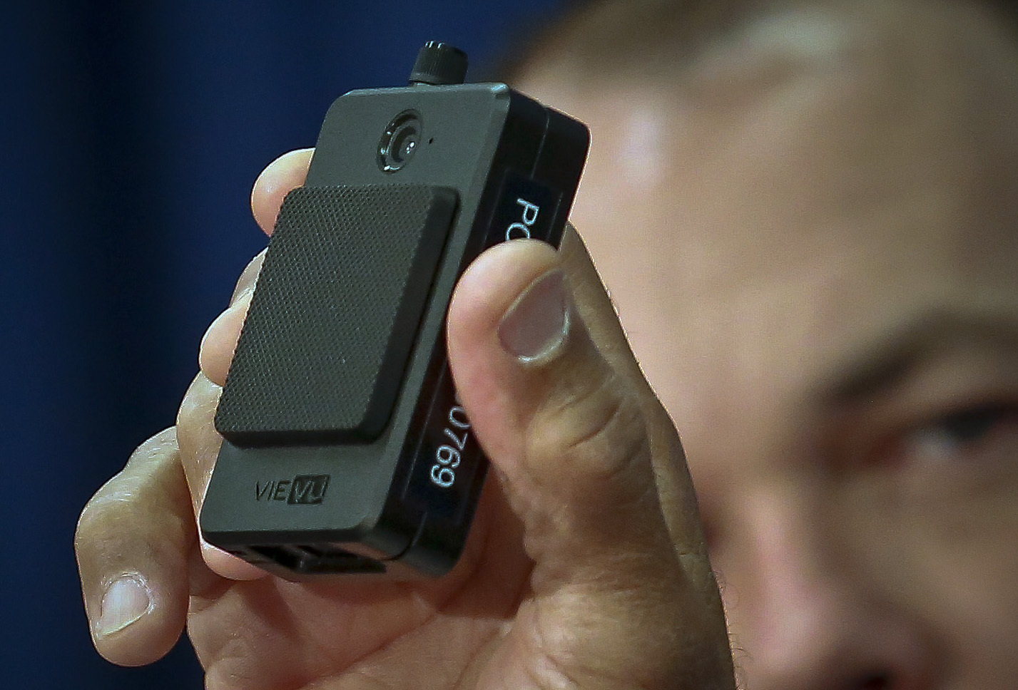 A man holds up a body camera to be used by the NYPD.