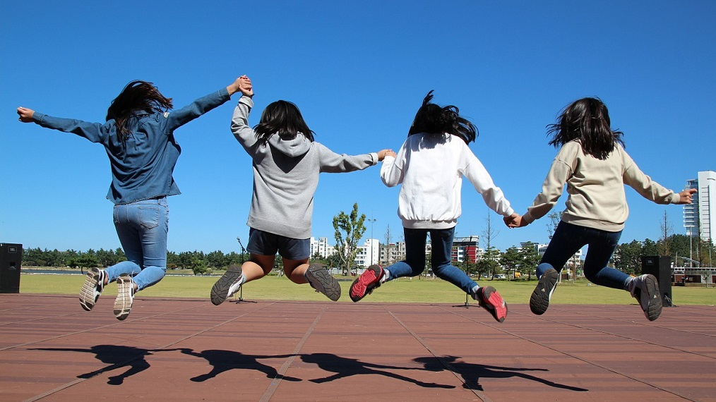 girls-holding-hands-jumping