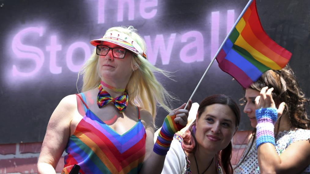Participants of the gay pride parade stand in front of the Stonewall Inn