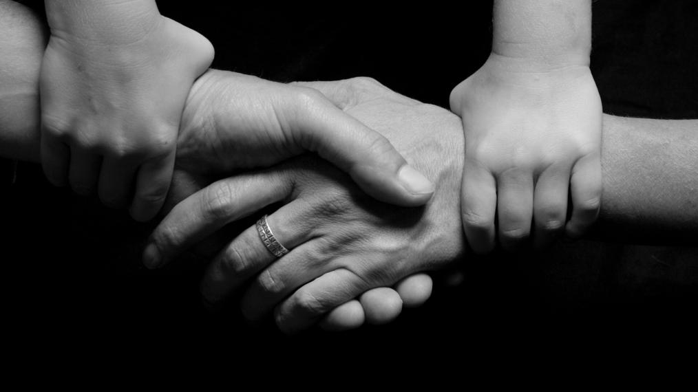 Black and White Child and Parent Holding Hands.